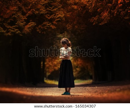 Art portrait of a lonely girl in the woods - stock photo