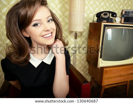 art portrait of young smiling ecstatic woman looking out at camera in room with vintage wallpaper and interior, retro stylization 60-70s, toned - stock photo