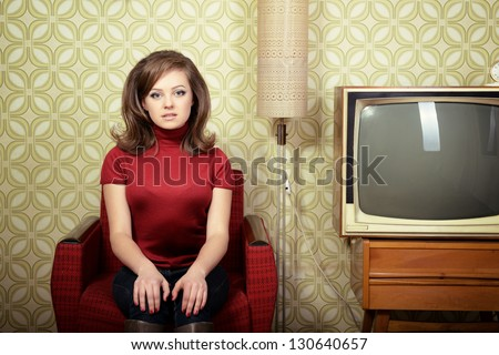 art portrait of young woman sitting on chair and looking at camera in room with vintage wallpaper and interior, retro stylization 60-70s, toned - stock photo