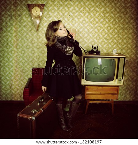 art portrait of young woman standing in room calling phone with vintage wallpaper and interior with tv, clocks, chair and suitcase, retro stylization 60-70s, toned - stock photo