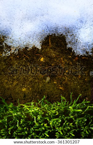 art Spring background with thawing snow and green grass - stock photo
