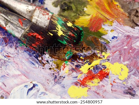 Art still life - two paintbrushes and dirty palette with colourful  paints,background for creative art design - stock photo