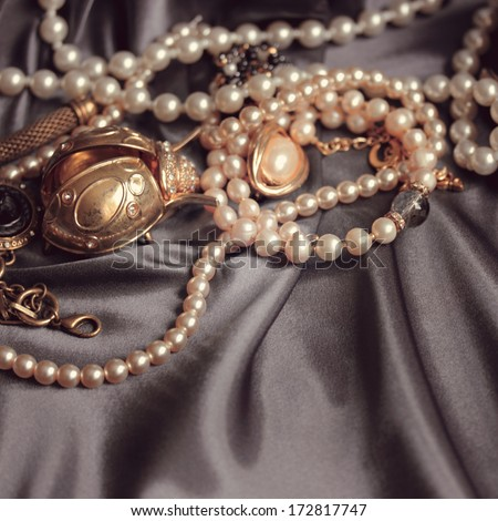 art vintage golden and pearl bijouterie with scarab on  gray silk background in peach sepia; square card  - stock photo