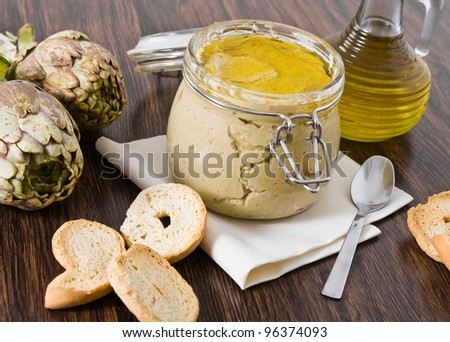 Artichoke pesto in glass jar. - stock photo