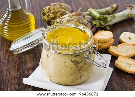 Artichoke pesto in glass jar. - stock photo