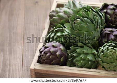 artichokes in wooden box - stock photo