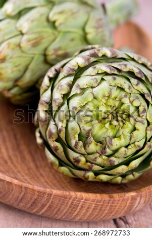 artichokes on old wooden surface - stock photo