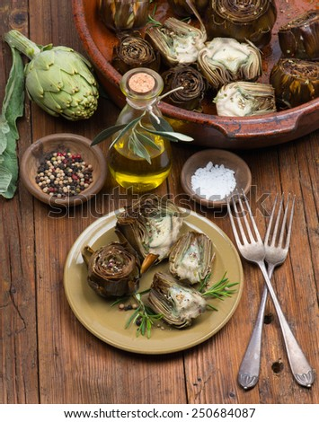 artichokes with spices on the wooden background - stock photo