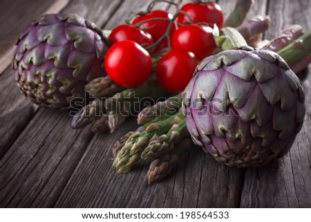 Artichokes with tomatoes and asparagus, selective focus - stock photo