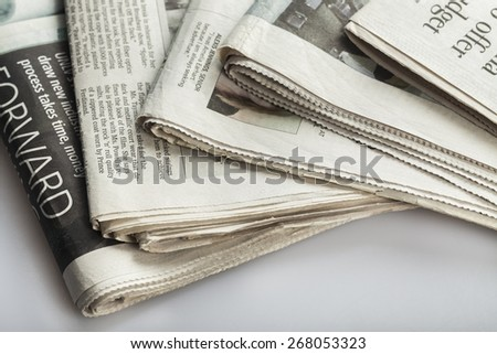 Article. Newspapers against plain background shot with very shallow depth of field - stock photo