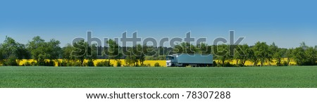 Articulated vehicle runs on an alley between adjacent fields in Brandenburg, Germany - stock photo