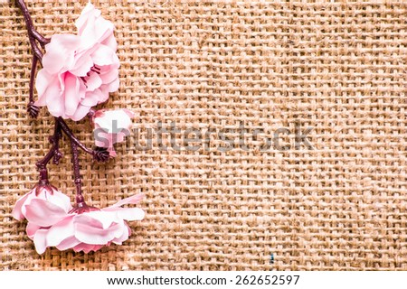 Artificial apple blossom isolated on burlap background useful as greeting card - stock photo
