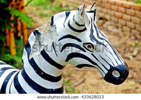 artificial broken zebra made from cement in the playground - stock photo
