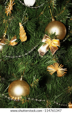 Artificial christmas tree decorated with golden balls and christmas decorations, close-up view, fragment - stock photo