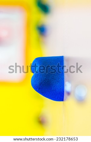 artificial climbing wall  in indoor children's playground, little gym, closeup look of blue grip - stock photo