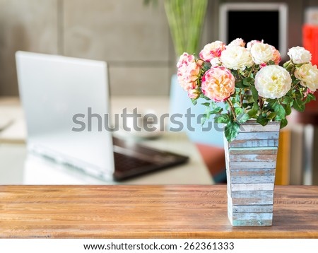 Artificial flower vase on table top over blurred image of  modern workplace background - stock photo