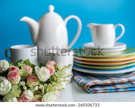Artificial flower with colorful dishware utensil on table top blurred background - stock photo