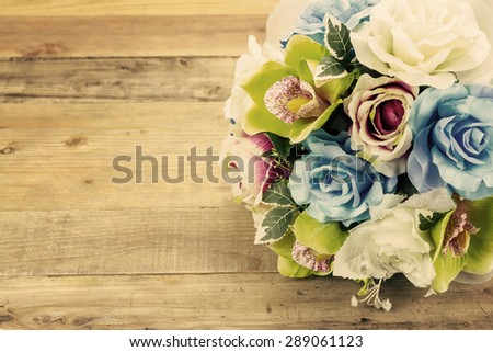 Artificial flowers on wooden background, Vintage effect - stock photo