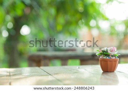 artificial mini pink paper rose on blur green garden background - stock photo