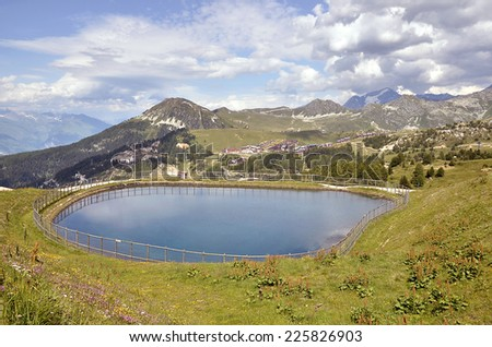 Artificial pond in the mountains of La Plagne, commune in the Tarentaise Valley,Savoie department and Rhone-Alpes region in France - stock photo