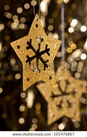 Artificial Snowflake in gold shining over a golden background - stock photo