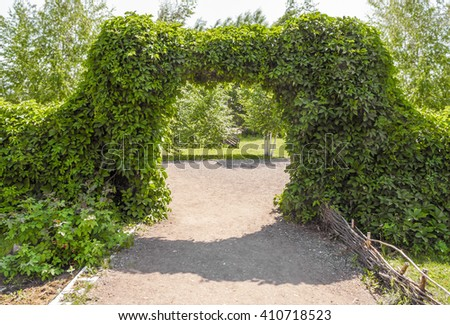 Artificially created ornamental garden arch of green bushes - stock photo