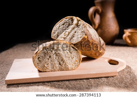 Artisan Baked Whole Grain Loaf of Bread Split in Half on Rustic Wooden Cutting Board on Table with Pitcher and Cup - stock photo
