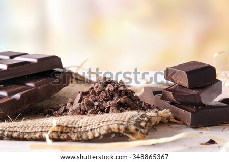 Artisan chocolate broken tablet stack with portions and chunks on a wooden table with decorative burlap and straw. Horizontal composition. Front view - stock photo
