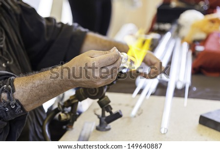 Artisan glass, detail of manual worker working with molten glass, craft and tradition - stock photo