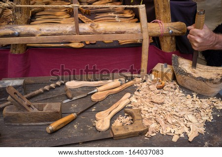 Artisan  hands at work, carving wood into spoons - stock photo
