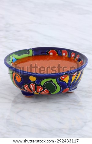 Artisan hot taco sauce in vintage talavera bowl, with a delicious fresh hot flavor,  on vintage carrara marble table. - stock photo