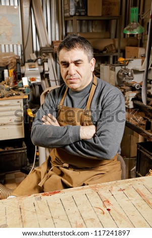 Artisan looking sideways sitting at workbench arms folded - stock photo