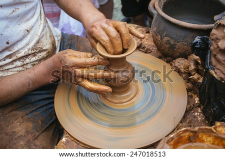 artisan potter molding a piece of clay on a lathe - stock photo