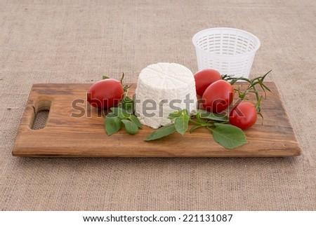 Artisan ricotta cheese with mould aka mold, tomatoes, basil. On wooden board,  hessian, burlap. - stock photo