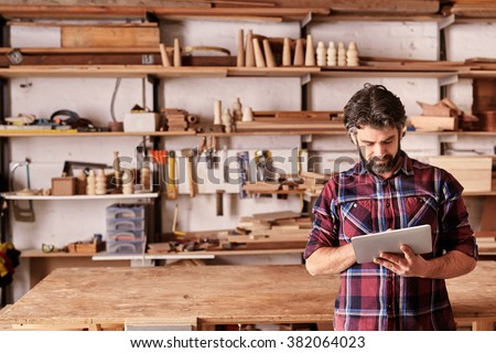 Artisan woodwork studio with shelving holding pieces of wood, with a carpenter standing in his workshop using a digital tablet - stock photo