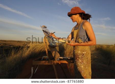 Artist at work on location in the Kalahari. - stock photo