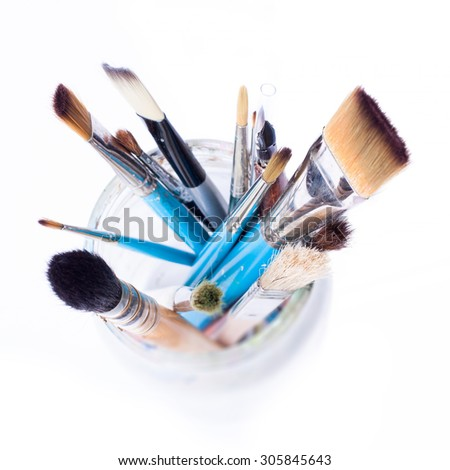 Artist brushes in a glass jar - view from the top. Isolated over white background. - stock photo