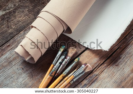 Artist canvas in roll and paint brushes on old rustic table - stock photo