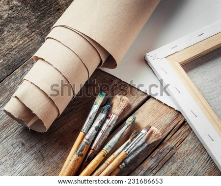 Artist canvas in roll, canvas stretcher and paintbrushes on old table - stock photo