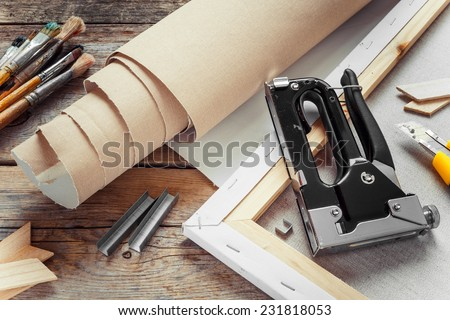 Artist canvas in roll, canvas stretcher, staple gun and paintbrushes on old table - stock photo