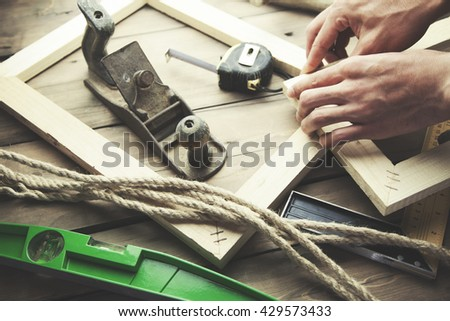 Artist canvas on man hand , canvas stretcher and staple gun on table - stock photo