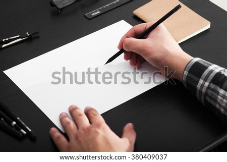 Artist drawing on a4 paper at the black table, stylish workplace - stock photo