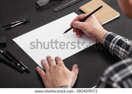 Artist draws on a white sheet of paper on a black table, stylish workplace - stock photo
