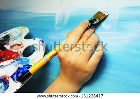 Artist  hand with paintbrush painting the picture - stock photo