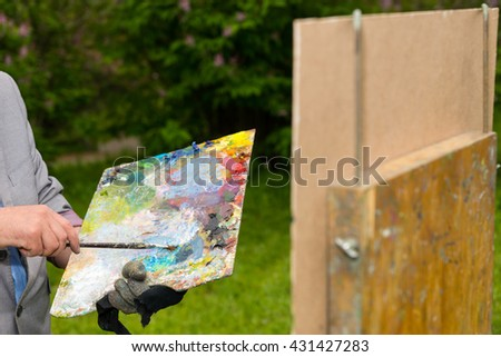 Artist holding a colorful palette and a paintbrush mixing colors in front of a sketchbook during an art class in a forest - stock photo