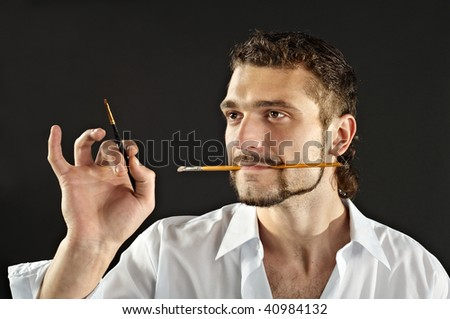 artist in a white shirt on a black background with a brush - stock photo