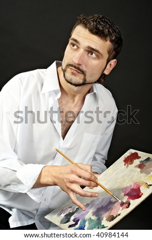 artist in a white shirt on a black background with a brush. Makes the outline of the palette. glance at - stock photo