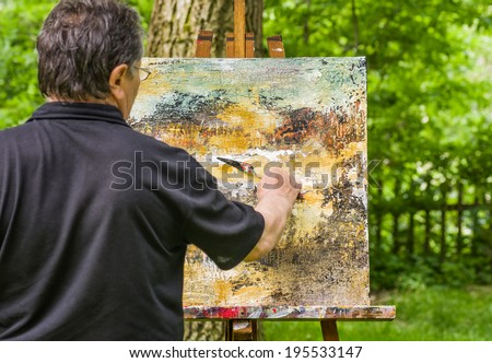 Artist is painting an abstract picture - stock photo