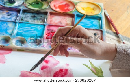 Artist is painting flower by watercolor on paper - stock photo