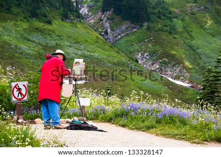 Artist outside in the field painting on his easel a landscape of the wildflowers in the mountains.  Copy space. - stock photo